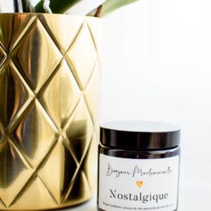 Nostalgique Scented Candle from Bonjour Mademoiselle with its lid on, sitting beside a gold plant pot