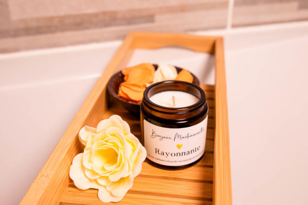 Rayonnante Scented Candle with lid off, sitting on a bath caddy with yellow flowers beside it