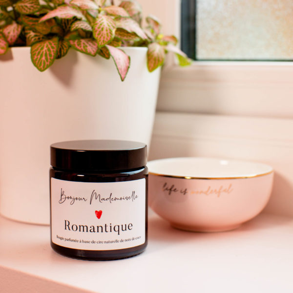 Romantique Scented Candle with the lid on, sitting beside a small trinket bowl and a white plant pot