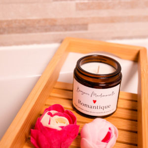 Romantique scented candle from Bonjour Mademoiselle sitting on a bath caddy beside two small soap flowers