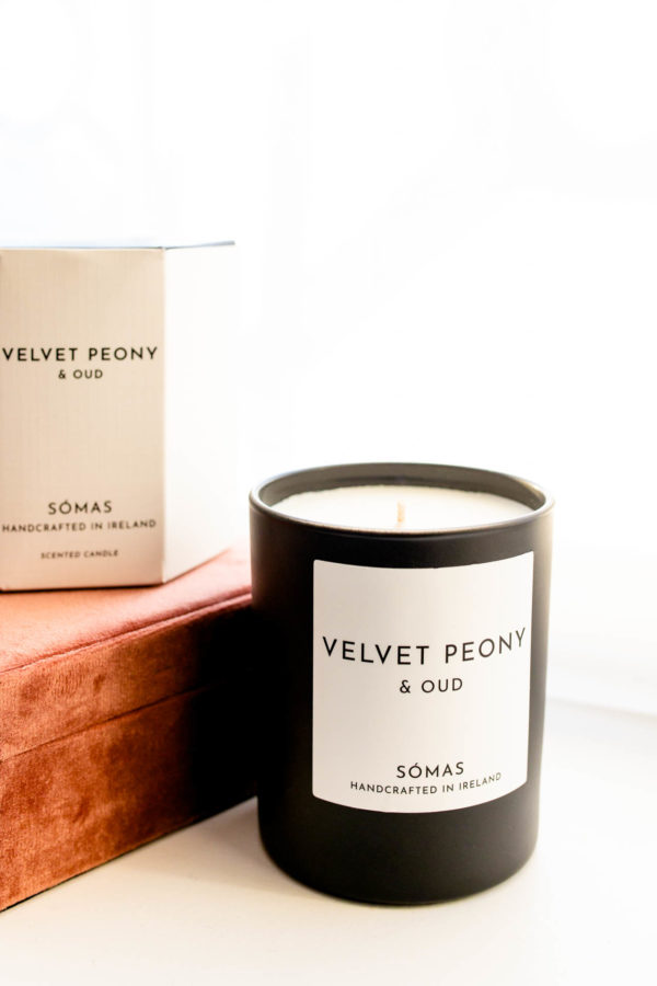 Velvet Peony and Oud candle in black container sitting beside a jewellery box