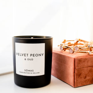 Velvet Peony and Oud Scented Candle in a black container sitting beside a jewellery box