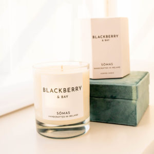 Blackberry and Bay scented candle from Somas sitting beside its box and a green jewellery box