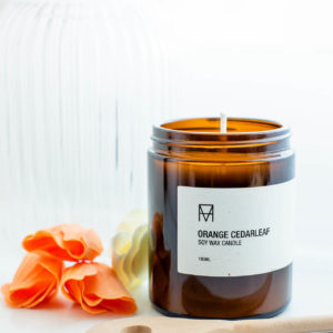 Orange and Cedar candle with a small pile or orange petals
