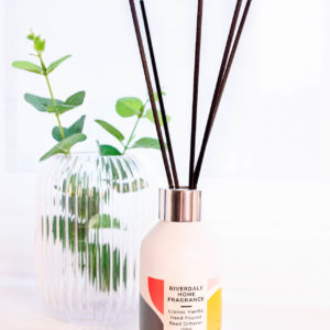 Vanilla Reed Diffuser with foliage beside in a glass vase