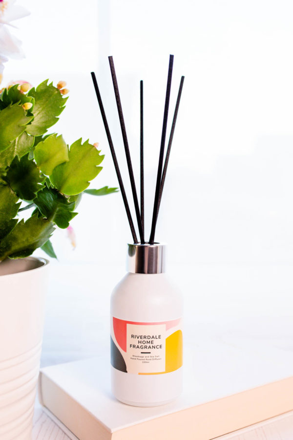 Woodsage and Sea Salt Diffuser with a plant beside
