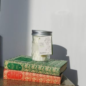 Clover Candle from Field Day sitting on top of two books