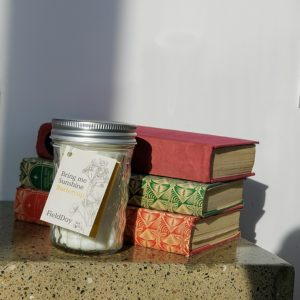 Buttercup Candle from Field Day sitting in front of three books