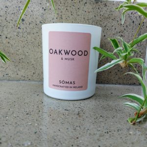 Oakwood and Musk Candle with green leaves alongside