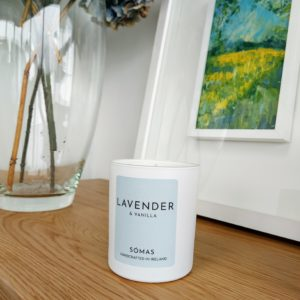 Image of Lavender and Vanilla Candle sitting in front of a painting