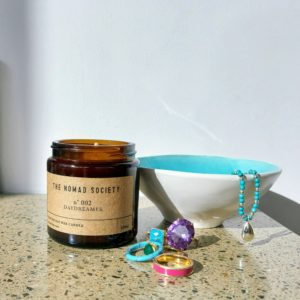 Daydreamer Scented Candle from Nomad Society, sitting beside a small bowl with jewellery alongside