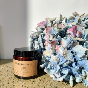 Libertine Scented Candle sitting beside a blue hydrangea flower