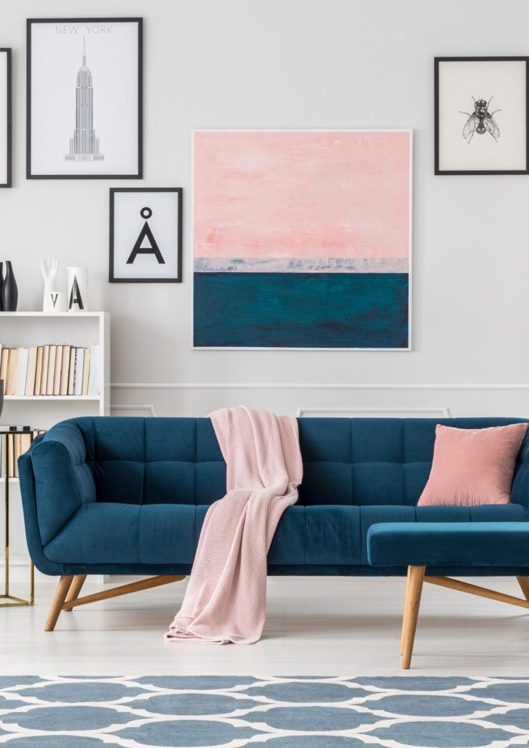 Image of living room with teal sofa and pink accents