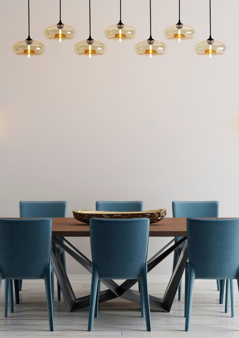 Image of dining room with teal chairs and brass lights
